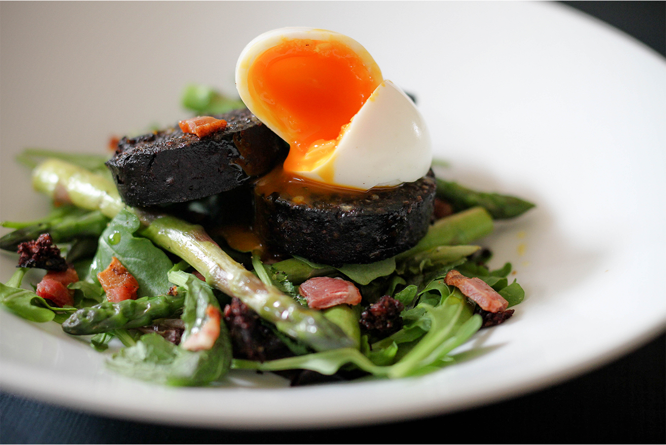 black pudding on a bed of salad and asparagus topped with a boiled egg