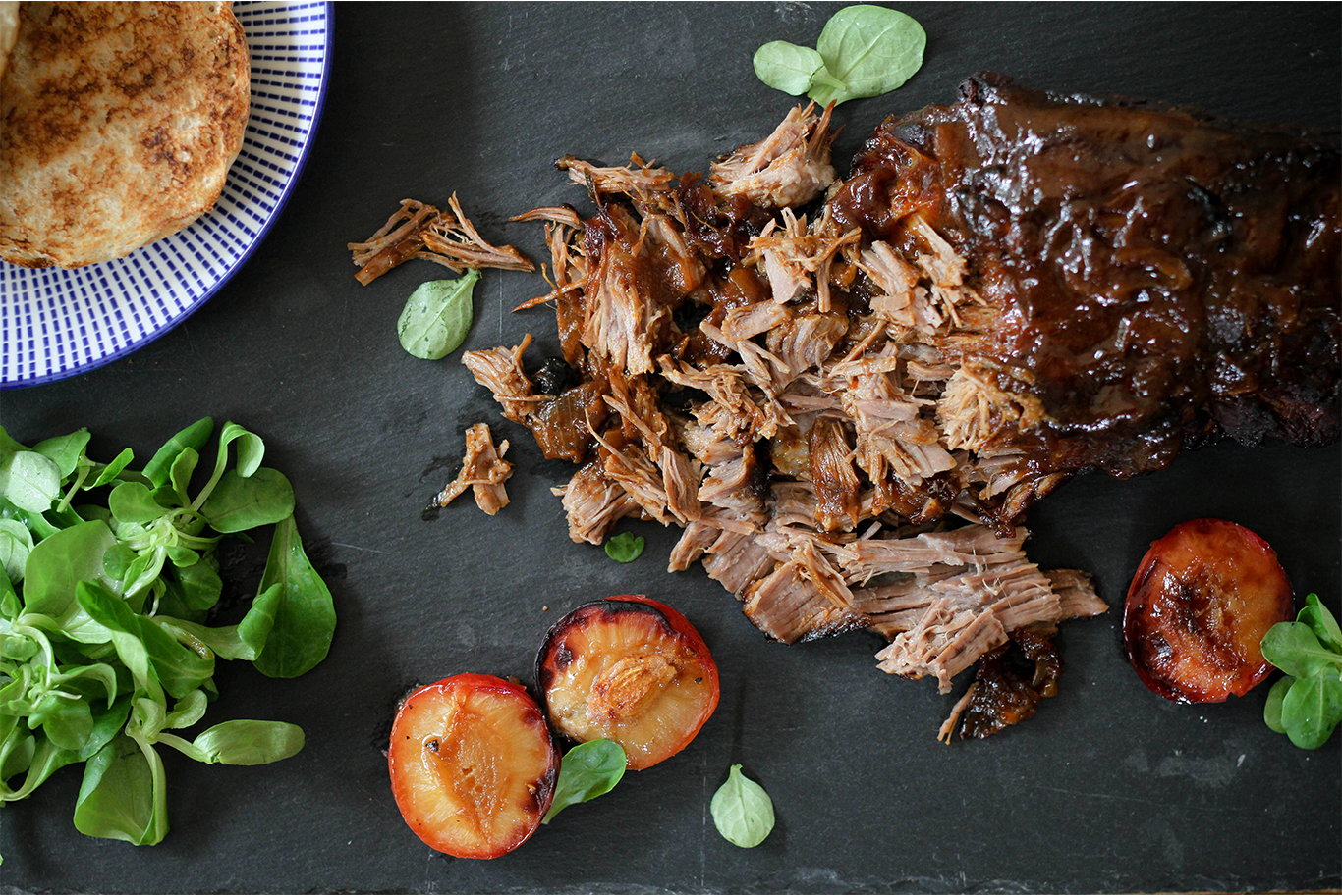 pulled pork on a black slate serving slab with lambs lettuce, toasted buns and caramelised plums